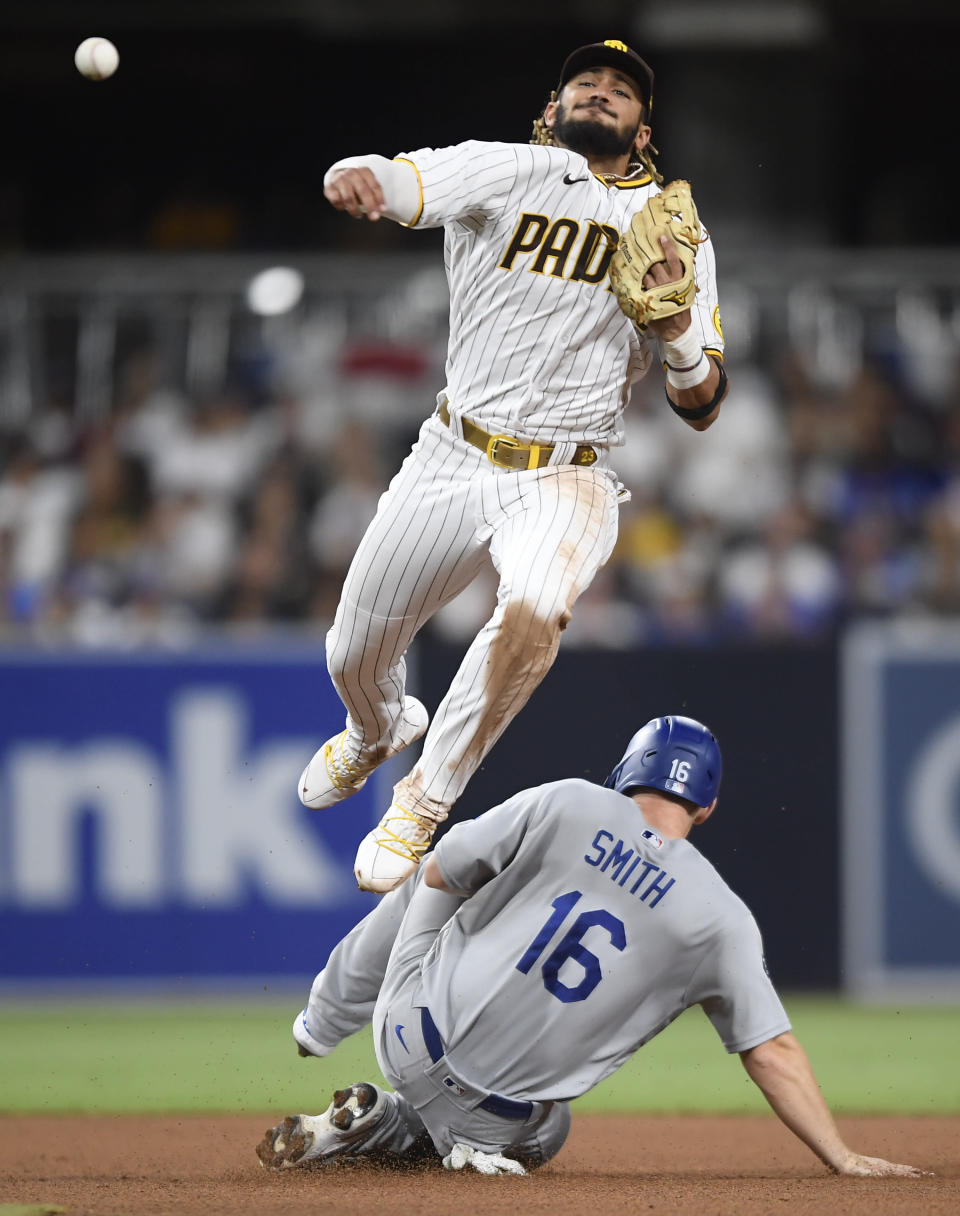 San Diego Padres shortstop Fernando Tatis Jr. (23) throws over Will Smith (16) as he tries to turn a double play during the fourth inning of a baseball game Wednesday, June 23, 2021, in San Diego. Tatis was unable to turn the double and was charged with a throwing error. (AP Photo/Denis Poroy)