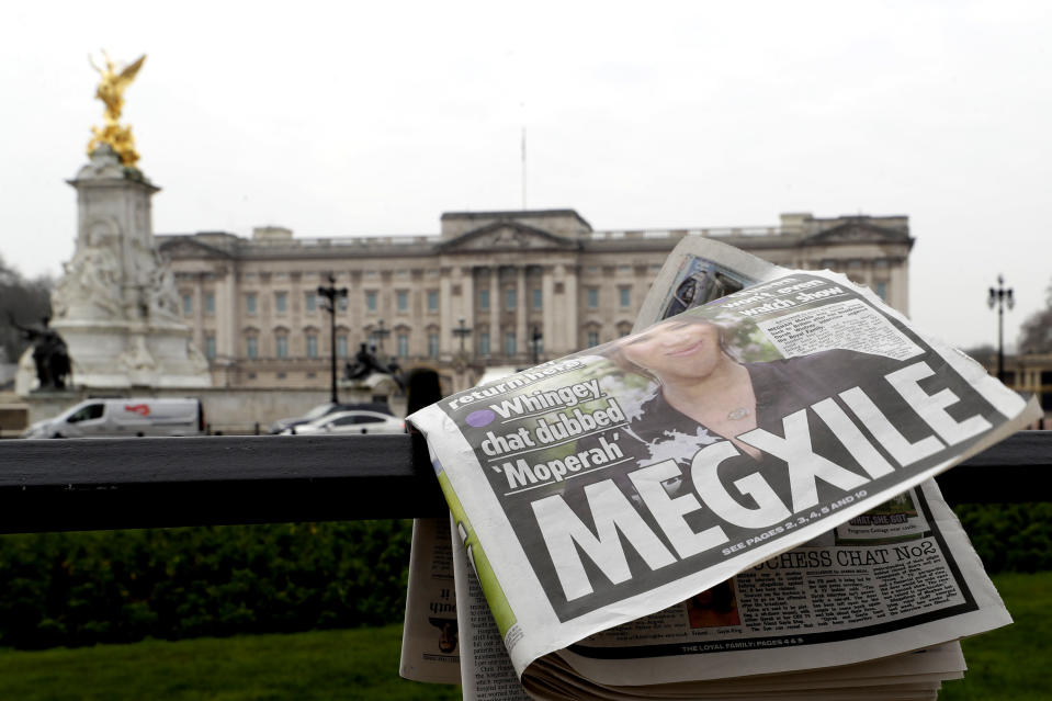 FILE - In this March 8, 2021, file photo, a newspaper is blown by the wind after it is placed on a railing by a television crew outside Buckingham Palace in London. Almost as soon as Meghan and Prince Harry's interview with Oprah Winfrey aired, many were quick to deny Meghan's allegations of racism on social media. Many say it was painful to watch Meghan's experiences with racism invalidated by the royal family, members of the media and the public, offering up yet another example of a Black woman's experience being disregarded and denied. (AP Photo/Kirsty Wigglesworth, File)