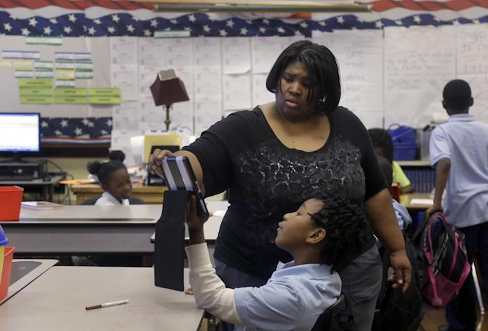 In this photo taken Wednesday, Nov. 13, 2013, Cynthia Williams works with students in her 4th grade class at Clay Elementary Community Education school in St. Louis. Williams is a participant in a pilot program called Home Works that sends public school teachers into their students' homes several times annually with the hope the home visits will boost both student academic achievement as well as parental involvement. (AP Photo/Jeff Roberson)