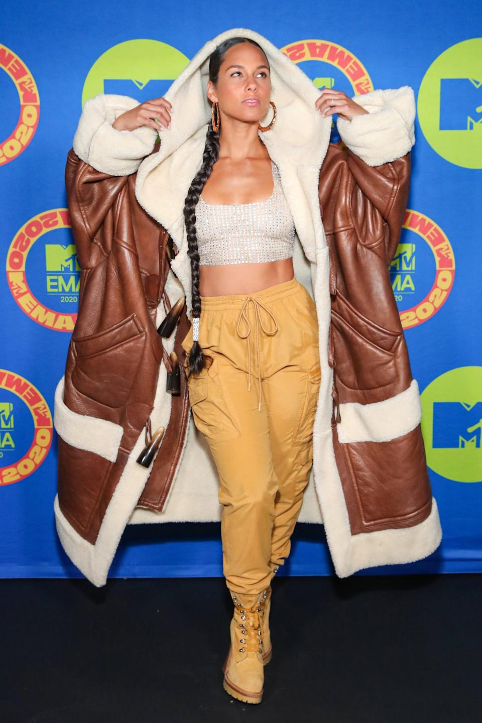 """<p><a class=""""link rapid-noclick-resp"""" href=""""https://www.popsugar.com/Alicia-Keys"""" rel=""""nofollow noopener"""" target=""""_blank"""" data-ylk=""""slk:Alicia Keys"""">Alicia Keys</a> wears a diamanté cropped top with khaki high-waisted cargo trousers, matching boots, and an oversize brown leather jacket with a white shearling trim.</p>"""