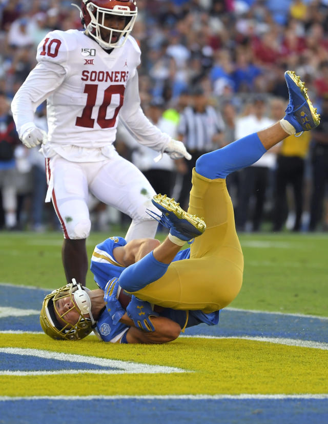 UCLA wide receiver Kyle Philips, below, dives in for a touchdown as Oklahoma safety Pat Fields watches during the first half of an NCAA college football game Saturday, Sept. 14, 2019, in Pasadena, Calif. (AP Photo/Mark J. Terrill)