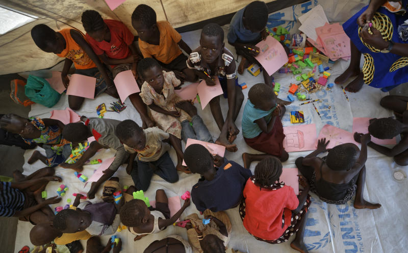 "FILE - In this Friday, June 9, 2017 file photo, unaccompanied or separated children play and draw on the floor of a World Vision tent as they wait for child protection specialists to evaluate their situations at the Imvepi reception center, where newly arrived refugees are processed before being allocated plots of land in nearby Bidi Bidi refugee settlement, in northern Uganda. The latest report on human rights abuses in South Sudan's five-year civil war, released by a United Nations commission Friday, Feb. 23, 2018 says it has identified more than 40 senior military officials ""who may bear individual responsibility for war crimes."" (AP Photo/Ben Curtis, File)"