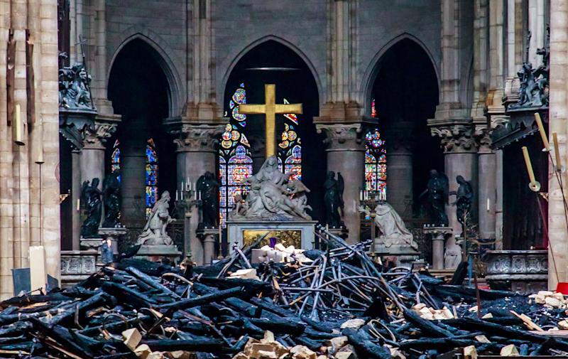 Blackened remains of Notre Dame's wooden roof framework lie on the cathedral floor. (Photo: POOL New / Reuters)