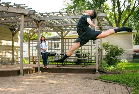 Handout photo of Roseville High School student Dmitri Moua practicing a dance routine in the backyard as his mother Bao Xiong looks on near Minneapolis, Minnesota