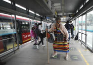 """Marlene Alfonso, a 69-year-old Venezuelan grandmother who goes by """"Toothless Cindy,"""" dances on a platform of the Transmilenio, the crowded and crime-ridden public bus system in Bogota, Colombia, Tuesday, Nov. 3, 2020. Her advanced age, comical lyrics, and unusual attire for a rapper have helped her to stand out and she has become an inspiration for a group of migrants who have been mostly welcomed in Colombia but have also suffered recently from discrimination and xenophobic attacks. (AP Photo/Fernando Vergara)"""