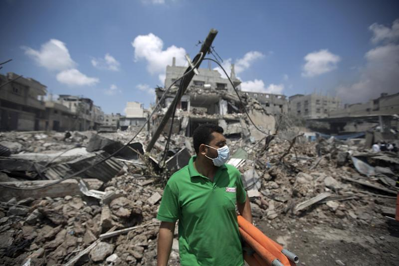 A Palestinian medic stands infront of a destroyed building in Gaza's eastern Shejaiya district, on July 20, 2014