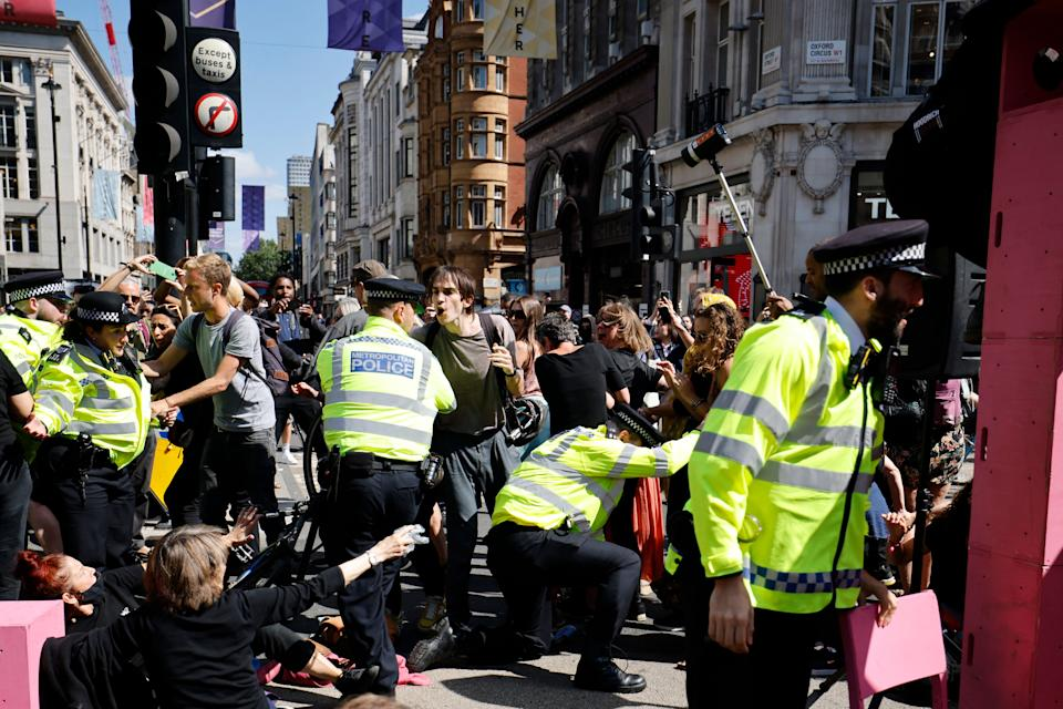 Police officers arrive as climate activists from the Extinction Rebellion group build a pink structure in the middle of Oxford Circus in central London on August 25, 2021 during the group's 'Impossible Rebellion' series of actions. - Climate change demonstrators from environmental activist group Extinction Rebellion continued with their latest round of protests in central London, promising two weeks of disruption. (Photo by Tolga Akmen / AFP) (Photo by TOLGA AKMEN/AFP via Getty Images)