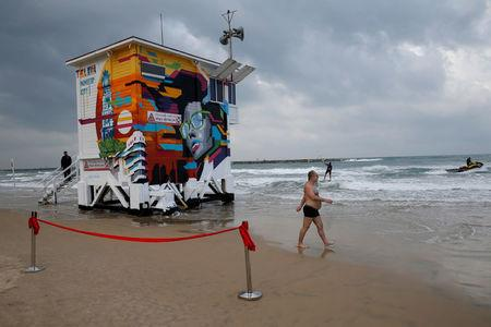 A beachgoer walks near a decorated lifeguard tower which was renovated into a luxury hotel suite as part of an international online competition, at Frishman Beach in Tel Aviv, Israel