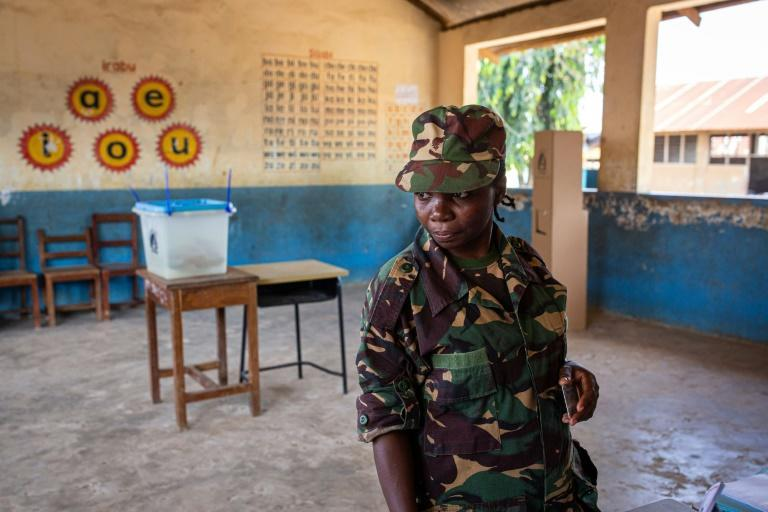 A Tanzanian security officer waits to cast her ballot in early voting