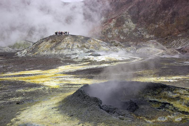 Tourists on White Island, North Island, New Zealand. Steam is seen rising from the ground.