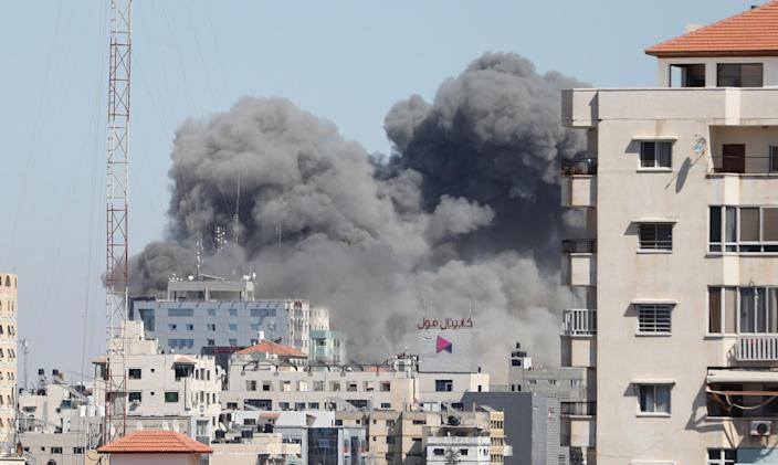 <p>Smoke rises after Israeli forces destroyed building in Gaza City where Al-Jazeera and Associated Press had their offices, on Saturday (15 May)</p> (Anadolu Agency/Getty)