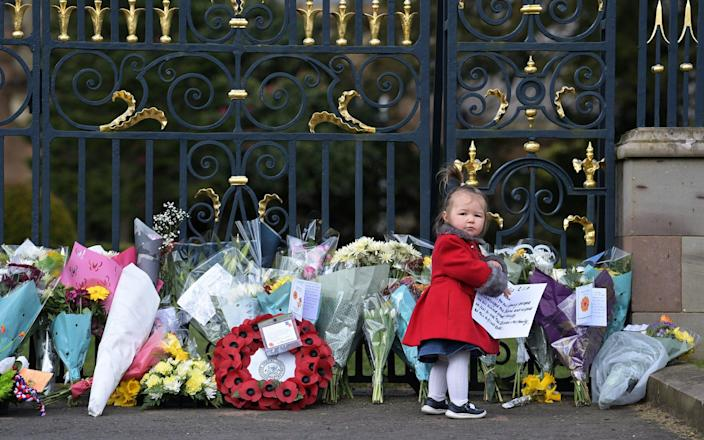 Masie Cairns, aged 18 months, looks at a card left at the gates of Hillsborough Castle - the Queen's official residence in Northern Ireland - Charles McQuillan/Getty