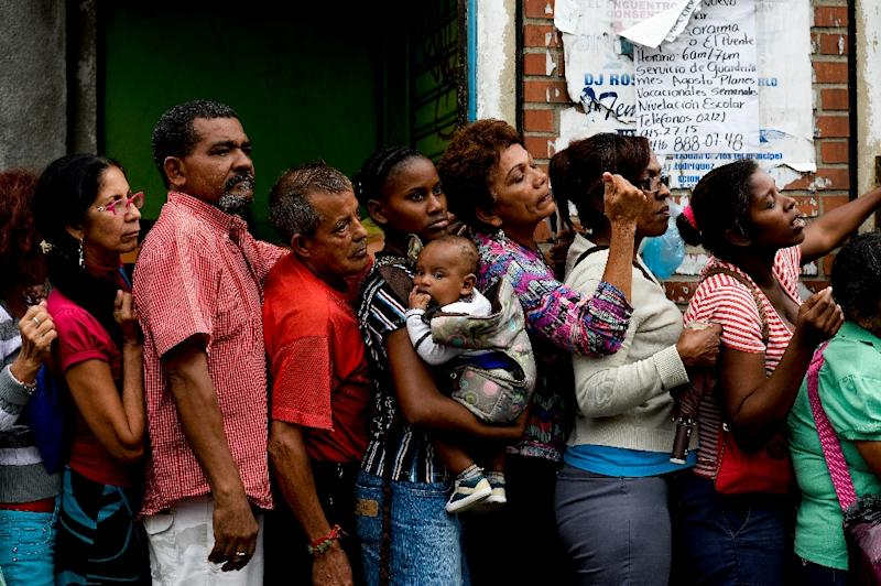 People queue up to buy food and basic household items at a supermarket in Caracas as Venezuela faces acute shortages