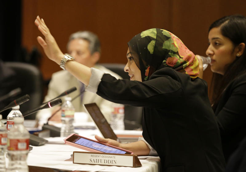 Sadia Saifuddin waves to fellow board members after taking her seat following confirmation at a University of California Board of Regents meeting Wednesday, July 17, 2013 in San Francisco. The University of California's governing board confirmed the first practicing Muslim student member to the board on Wednesday, despite opposition from some Jewish groups. UC regents voted in favor of UC Berkeley student Sadia Saifuddin's nomination. One regent, Richard Blum, abstained from the vote. At right looking on is student regent Cinthia Flores. (AP Photo/Eric Risberg)