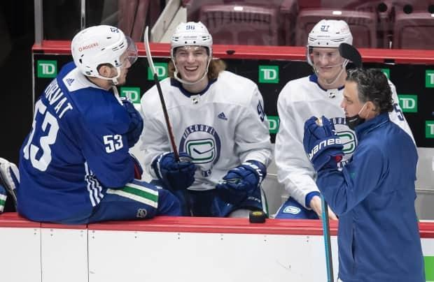 Adam Gaudette laughs while on the bench with Bo Horvat, left, and Tyler Myers, as head coach Travis Green skates past. Gaudette was the first Canucks player to test positive for COVID-19 on March 30.  (Darryl Dyck/The Canadian Press - image credit)
