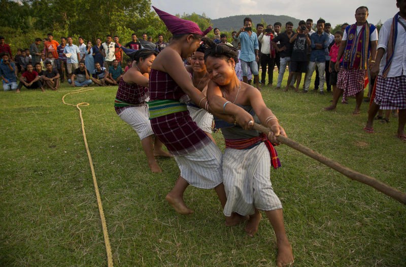 In this Monday, June 10, 2019 photo, Indian Rabha tribal Hindu women participate in tug of war during Baikho festival at Pantan village, west of Gauhati, India. Every year, the community in India's northeastern state of Assam celebrates the festival, to please a deity of wealth and ask for good rains and a good harvest. (AP Photo/Anupam Nath)