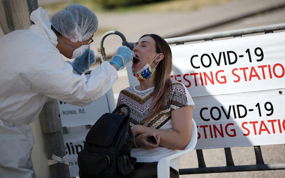 A health worker takes a swab from a woman at a mobile testing station for coronavirus disease in Almaty, Kazakhstan - Pavel Mikheyev/Reuters