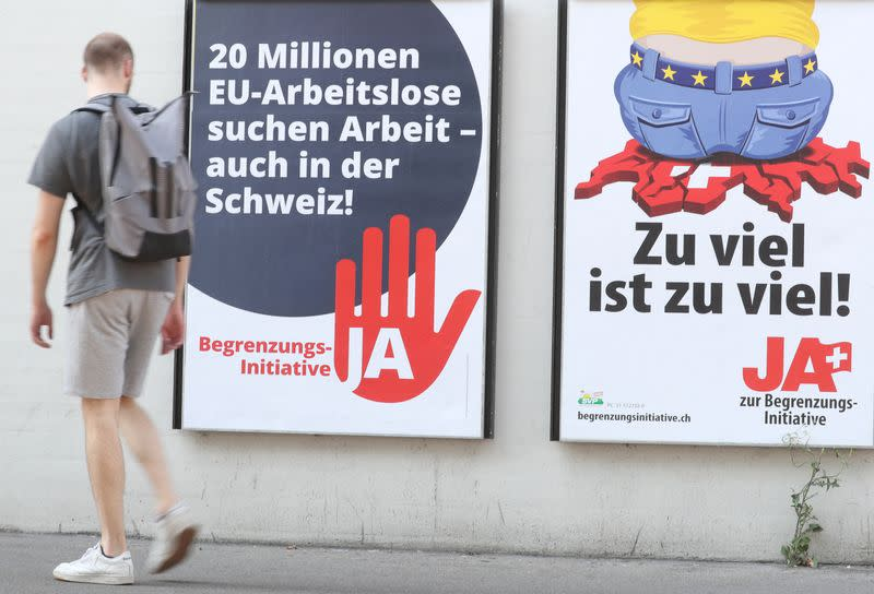 FILE PHOTO:Man walks past posters against the anti-immigration initiative in Zurich