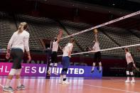 Right side hitter Karsta Lowe, second from right, delivers a hit during volleyball practice in Dallas, Wednesday, Feb. 24, 2021. U.S. Olympian Lowe is playing competitive volleyball again for the first time since the pandemic had her scrambling to get home from a pro league in Italy a year ago. Lowe is part of a unique, player-run American venture first tried with softball near Chicago last summer. A five-week season that emphasizes individuals over teams starts this weekend. (AP Photo/Tony Gutierrez)