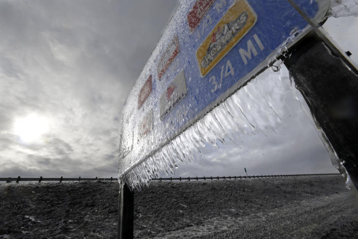 Icicles, formed by freezing rain and stiff winds, hang from a road sign along Interstate 84 as the sun tries to break through dark clouds in Troutdale, Ore., Wednesday, Jan. 18, 2017. An ice storm shut down parts of major highways and interstates Wednesday in Oregon and Washington state and paralyzed the hardest hit towns along the Columbia River Gorge with up to 2 inches of ice coating the ground in some places. (AP Photo/Don Ryan)
