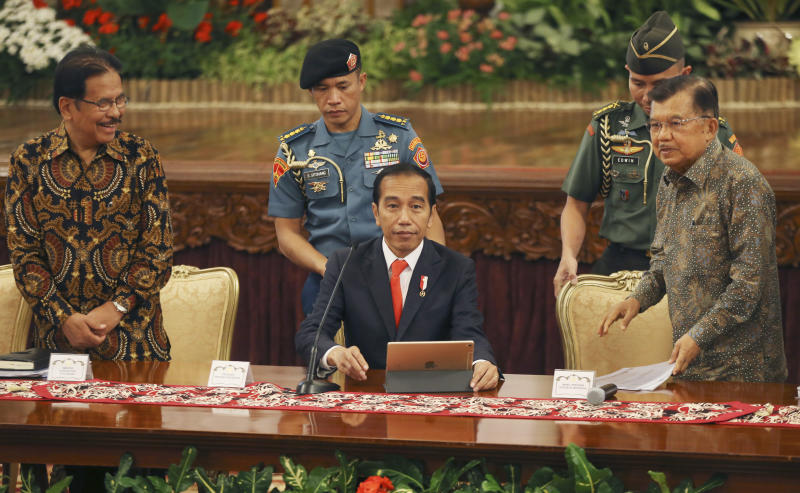 Indonesia President Joko Widodo, center, takes his seat as his deputy Jusuf Kalla, right, and Agrarian and Spatial Planning Minister Sofyan Djalil, left, looks on before a press conference, at the palace in Jakarta, Indonesia, Monday, Aug. 26, 2019. Indonesia's president has announced to relocate the country's capital from overcrowded, sinking and polluted Jakarta to East Kalimantan province. (AP Photo/Achmad Ibrahim)