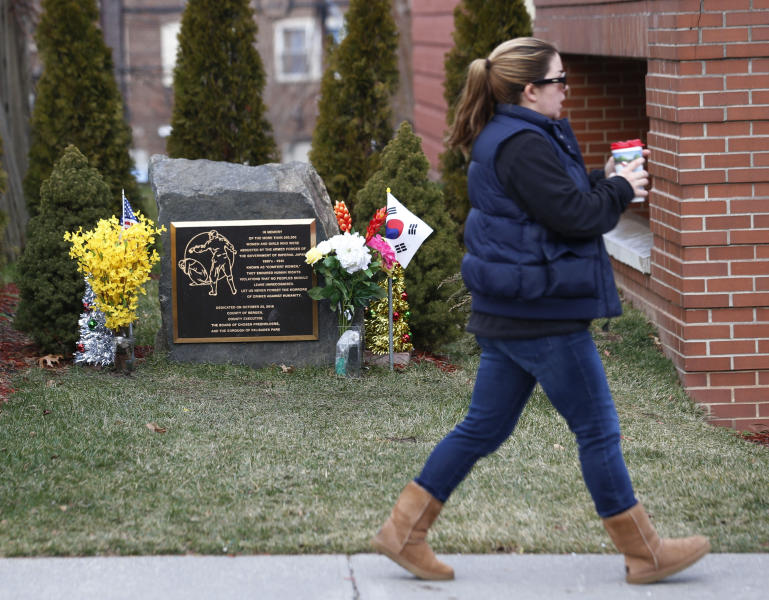 A memorial, left, honoring comfort women of WWII stands at a distance while a woman walks to the adjacent public library, Thursday, Jan. 17, 2013, in Palisades Park, N.J. Comfort women refers to the women mostly from the Korean peninsula and China who were forced to provide sex for Japanese soldiers during WWII. A dispute has risen over different historical definitions of the so-called comfort women. Japan's current nationalist Prime Minister has suggested he may disavow a 1993 apology for the practice, and Japanese government officials even tried pressuring the small Palisades Park town to remove its memorial, which was the first of its kind in the U.S. Now, the backers of that memorial are planning to unveil a second one at the Bergen County Courthouse in Hackensack, N.J., and engaging in an education campaign around the issue. (AP Photo/Julio Cortez)