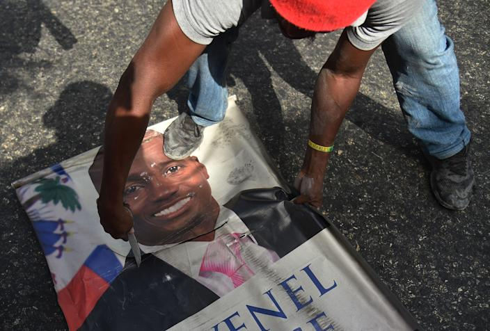 <p>Protesters destroy a poster of Haitian President Jovenel Moise as they demonstrate in the Port-au-Prince suburb of Petion-Ville on July 7, 2018, against a hike in fuel prices. (Photo: Hector Retamal/AFP/Getty Images) </p>