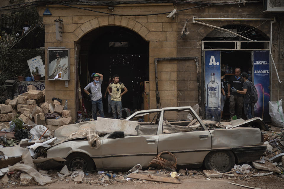People stand next to a car damaged by Tuesday's explosion in the seaport of Beirut, Lebanon, Friday, Aug. 7, 2020. Rescue teams were still searching the rubble of Beirut's port for bodies on Friday, nearly three days after the massive explosion sent a wave of destruction through Lebanon's capital. (AP Photo/Felipe Dana)