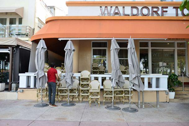 PHOTO: A man is seen stacking up chair of a closed restaurant on Ocean Drive in the entertainment district of Miami Beach on July 20, 2020 in Miami Beach, Florida. (Johnny Louis/Getty Images)