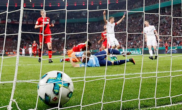 Soccer Football - DFB Cup - Bayer Leverkusen vs Bayern Munich - BayArena, Leverkusen, Germany - April 17, 2018 Bayern Munich's Thomas Mueller celebrates scoring a goal as Bayer Leverkusen's Bernd Leno looks on REUTERS/Wolfgang Rattay DFB RULES PROHIBIT USE IN MMS SERVICES VIA HANDHELD DEVICES UNTIL TWO HOURS AFTER A MATCH AND ANY USAGE ON INTERNET OR ONLINE MEDIA SIMULATING VIDEO FOOTAGE DURING THE MATCH.