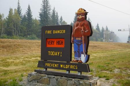 A Smokey the Bear sign warns of very high wildfire risk along the Seward Highway, near where the Swan Lake Fire near Seward