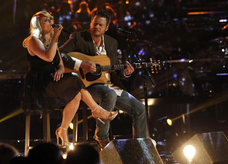 "This May 21, 2013 photo released by NBC shows married singers Miranda Lambert, left, and  Blake Shelton performing an acoustic version of the hit ""Over You"" during a broadcast of the singing competition series, ""The Voice,"" in Los Angeles. Shelton and NBC are putting together a benefit for Oklahoma tornado victims. Shelton, an Oklahoma native, told reporters about the fundraising effort after Tuesday night's episode of ""The Voice."" He said the benefit would be held soon in nearby Oklahoma City.  (AP Photo/NBC, Trae Patton)"