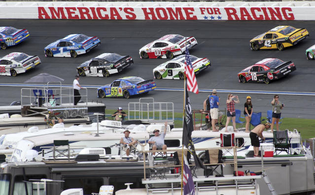 FILE - In this Sept. 29, 2018, file photo, fans watch as drivers race during the NASCAR Xfinity series auto race at Charlotte Motor Speedway in Concord, N.C. Some fans have been coming to the Coca-Cola 600 for decades, but they won't be allowed into Charlotte Motor Speedwaý on Sunday due to Covid-19, leaving the grandstands empty and many disappointed. (AP Photo/Bob Jordan, File)