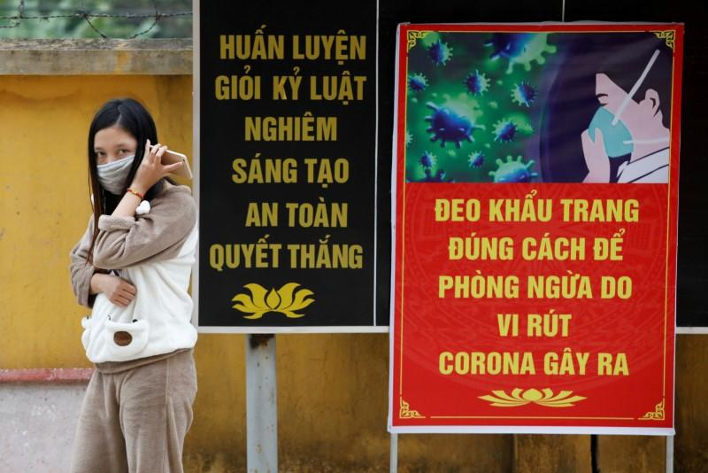 FILE PHOTO: Vietnamese woman who came back from China wears a protective mask while talking on the phone with a relative inside a quarantine area at a military base in Lang Son province
