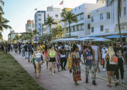 FILE - Spring break tourists walk alongside Ocean Drive in Miami Beach, Fla., on March 21, 2021, as a curfew has been extended in Miami Beach after law enforcement worked to contain unruly crowds of spring break tourists. (Carl Juste/Miami Herald via AP, File)