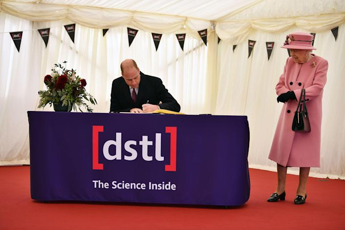 Britain's Queen Elizabeth II (R) stands by as Britain's Prince William, Duke of Cambridge (L) signs a visitor's book during their visit to the Defence Science and Technology Laboratory (Dstl) at Porton Down science park near Salisbury, southern England, on October 15, 2020. - The Queen and the Duke of Cambridge visited the Defence Science and Technology Laboratory (Dstl) where they were to view displays of weaponry and tactics used in counter intelligence, a demonstration of a Forensic Explosives Investigation and meet staff who were involved in the Salisbury Novichok incident. Her Majesty and His Royal Highness also formally opened the new Energetics Analysis Centre. (Photo by Ben STANSALL / POOL / AFP) (Photo by BEN STANSALL/POOL/AFP via Getty Images)