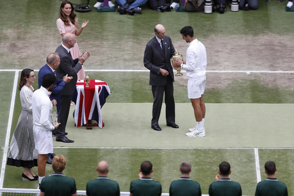 The Duke of Kent presents Serbia's Novak Djokovic with the winners trophy after he defeated Italy's Matteo Berrettini in men's singles final on day thirteen of the Wimbledon Tennis Championships in London, Sunday, July 11, 2021. At top left is Kate, Duchess of Cambridge. (Pete Nichols/Pool Via AP)