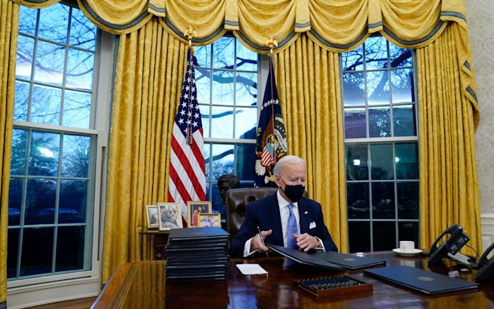 President Joe Biden signs his first executive orders in the Oval Office - Evan Vucci /AP