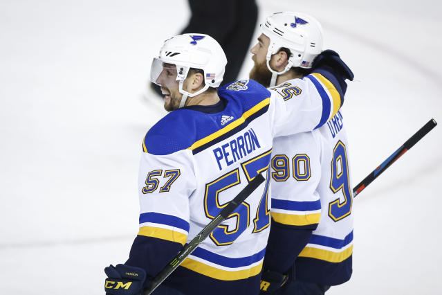 St. Louis Blues' David Perron, left, celebrates his game-winning goal with teammate Ryan O'Reilly during overtime of an NHL hockey game against the Calgary Flames in Calgary, Saturday, Nov. 9, 2019. (Jeff McIntosh/The Canadian Press via AP)