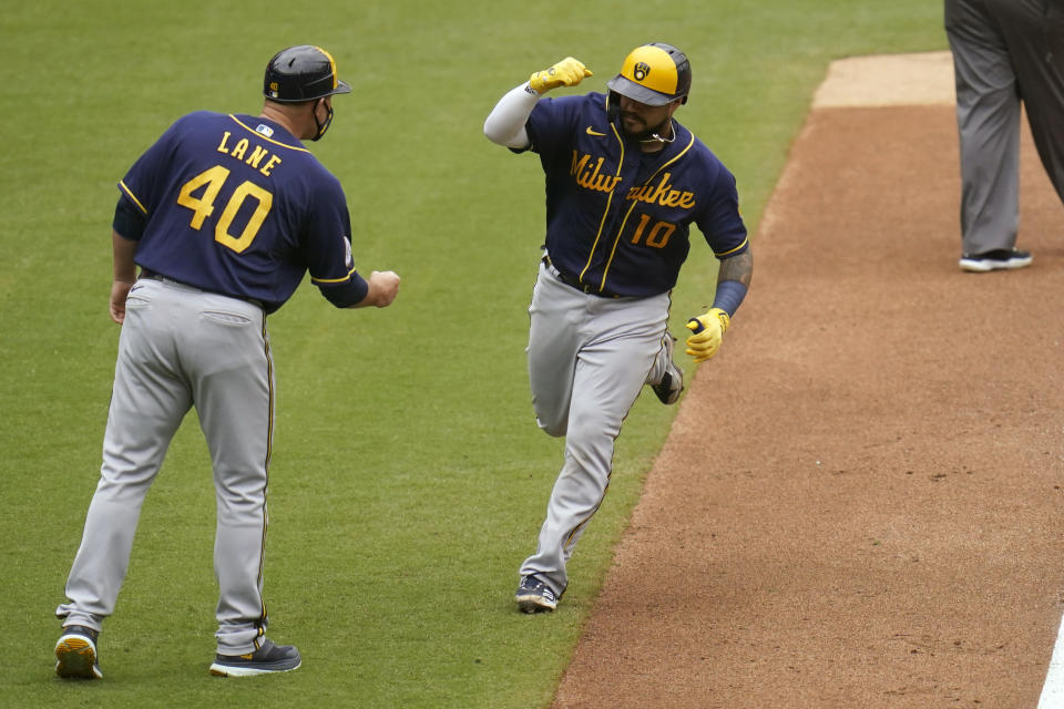 Milwaukee Brewers' Omar Narvaez reacts with third base coach Jason Lane (40) after hitting a two-run home run during the sixth inning of a baseball game against the San Diego Padres, Wednesday, April 21, 2021, in San Diego. (AP Photo/Gregory Bull)