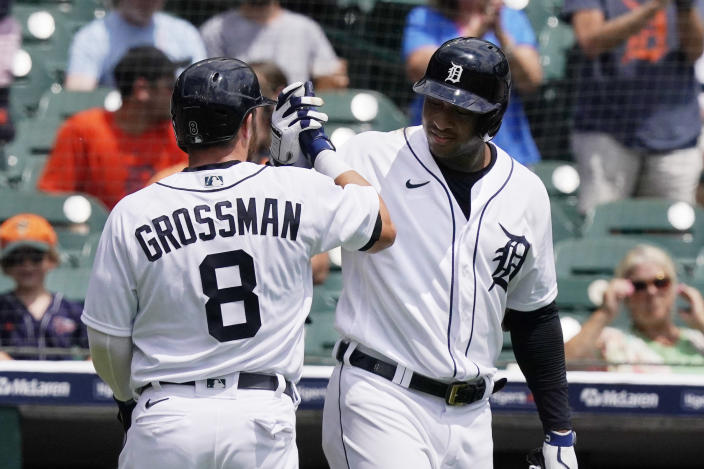 Detroit Tigers right fielder Robbie Grossman is greeted by Jonathan Schoop after hitting a solo home run during the first inning of the first baseball game of a doubleheader against the Minnesota Twins, Saturday, July 17, 2021, in Detroit. (AP Photo/Carlos Osorio)