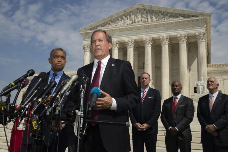 Texas Attorney General Ken Paxton, center, with District of Columbia Attorney General Karl Racine, left, and a bipartisan group of state attorneys general speaks to reporters in front of the U.S. Supreme Court in Washington, Monday, Sept. 9, 2019 on an antitrust investigation of big tech companies. (AP Photo/Manuel Balce Ceneta)