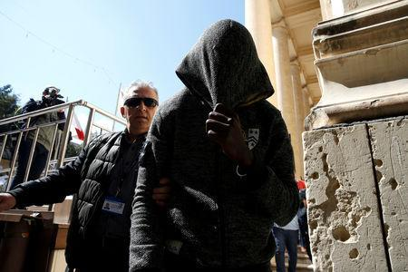 One of the migrants charged with hijacking the merchant ship El Hiblu 1 is escorted by a police officer out of the Courts of Justice in Valletta, Malta, March 30, 2019. REUTERS/Darrin Zammit Lupi/Files
