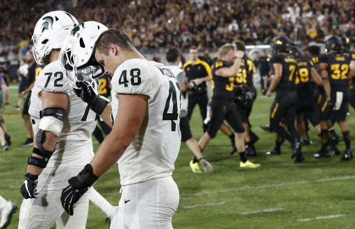 FILE - In this Saturday, Sept. 8, 2018, file photo, Arizona State players celebrate a game-winning field goal as Michigan State's Kenny Willekes (48) and Mike Panasiuk (72) walk off the field at the end after an NCAA college football game, in Tempe, Ariz. Arizona State defeated Michigan State 16-13. The last two Big Ten champions didn't make college football's playoff, in part because of early losses against tough non-conference foes. This year, Michigan State and Michigan have already dropped games, reducing their margins for error and raising again the question of whether playing tough teams out of conference is worth the risk (AP Photo/Ross D. Franklin, File)