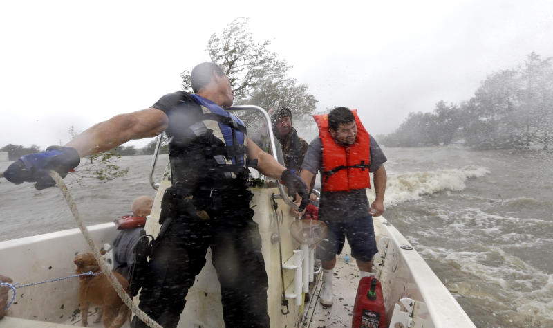 Drug Enforcement Agency Special Agent Keith Billiot, left, Lanny LaFrance, center, and Sam Maltese, right, battle the wind and rain from Hurricane Isaac while riding in a rescue boat Wednesday, Aug. 29, 2012, in Braithwaite, La. Maltese and his family were rescued from their flooded home. (AP Photo/David J. Phillip)