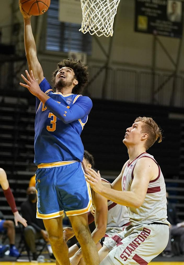 UCLA's Johnny Juzang drives to the basket against Stanford's Lukas Kisunas during the second half Jan. 23, 2021.