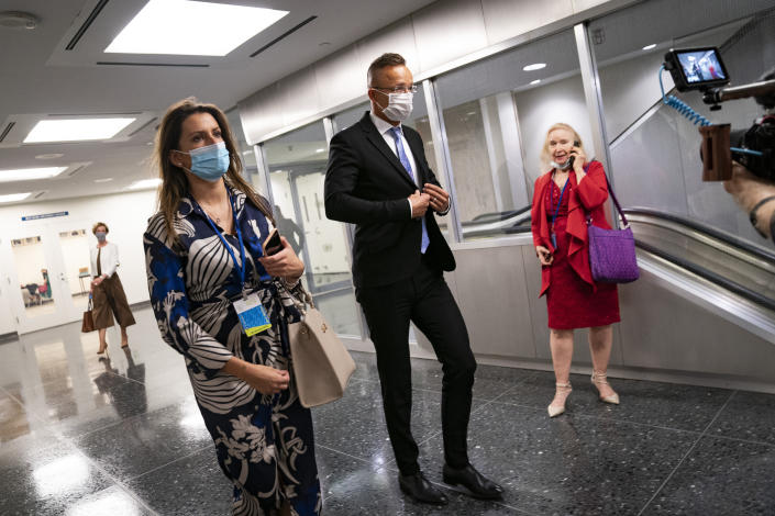Peter Szijjarto, Hungary's minister of foreign affairs and trade, center, arrives for an interview with the Associated Press at United Nations headquarters, Thursday, Sept. 23, 2021, during the 76th Session of the U.N. General Assembly in New York. (AP Photo/John Minchillo)