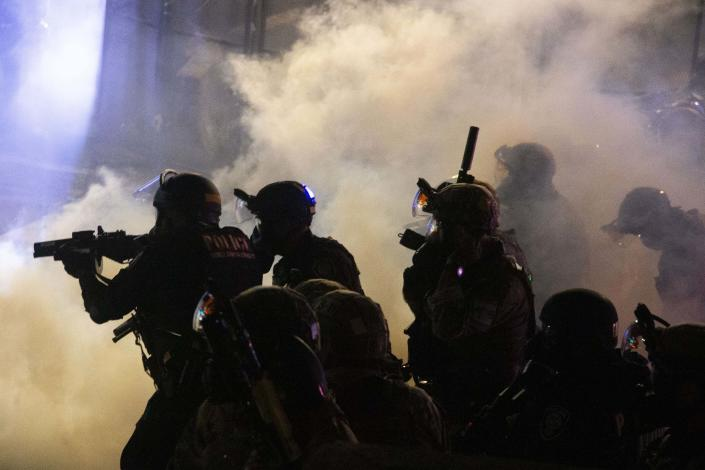 Federal officers use chemical irritants and projectiles to disperse Black Lives Matter protesters early late Thursday, July 23, 2020, in Portland, Ore. Since federal officers arrived in downtown Portland in early July, violent protests have largely been limited to a two block radius from the courthouse. (Beth Nakamura /The Oregonian via AP)