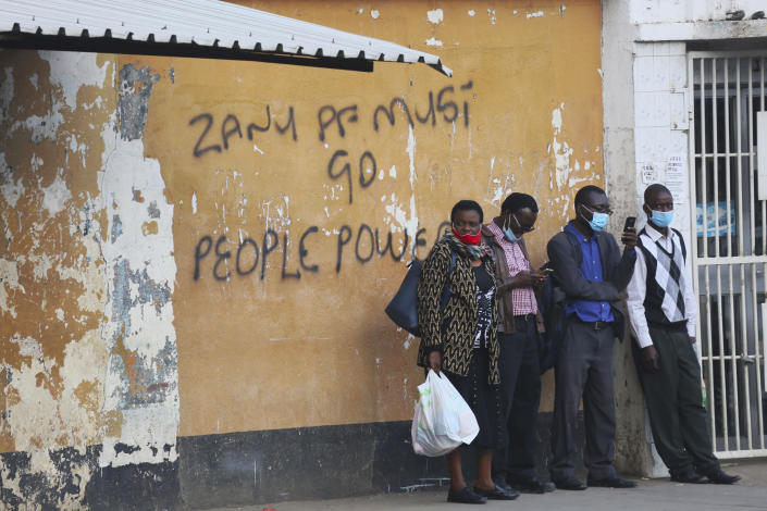 "People wait for public transport at a bus stop with graffiti calling on the ruling Zanu pf party to resign in this Monday, June, 15, 2020 photo. Unable to protest on the streets, some in Zimbabwe are calling themselves ""keyboard warriors"" as they take to graffiti and social media to pressure a government that promised reform but is now accused of gross human rights abuses.(AP Photo/Tsvangirayi Mukwazhi)"