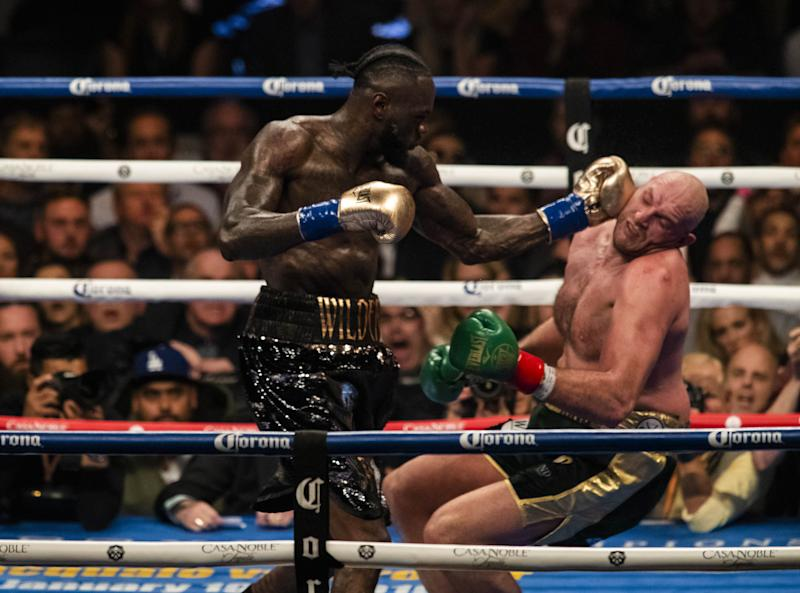 LOS ANGELES, USA - DECEMBER 01: Deontay Wilder (L) lands a left hook and knocks down Tyson Fury (R) in the 12th round of WBC Heavyweight Championship at the Staples Center in Los Angeles, California on December 01, 2018. (Photo by Philip Pacheco/Anadolu Agency/Getty Images)